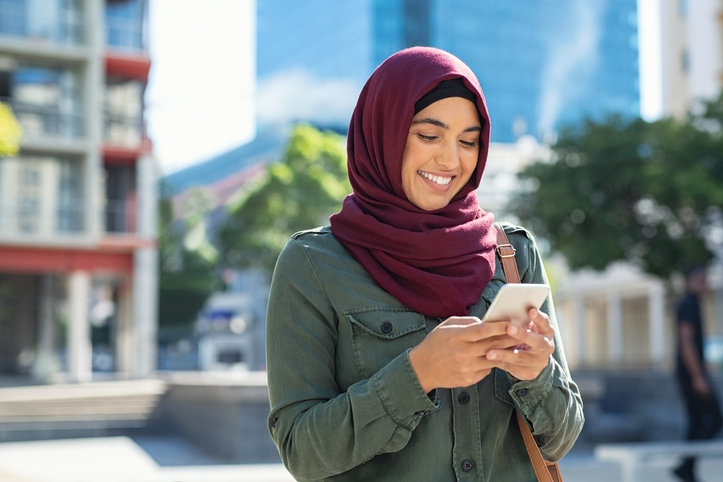Woman in head scarf looking at phone
