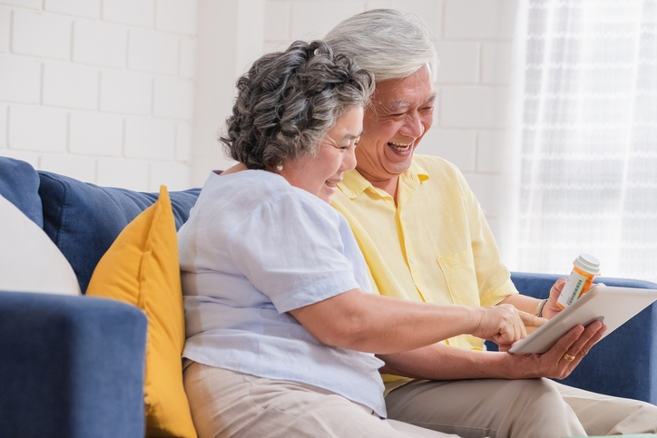 Smiling older Asian couple doing a telehealth visit on their couch