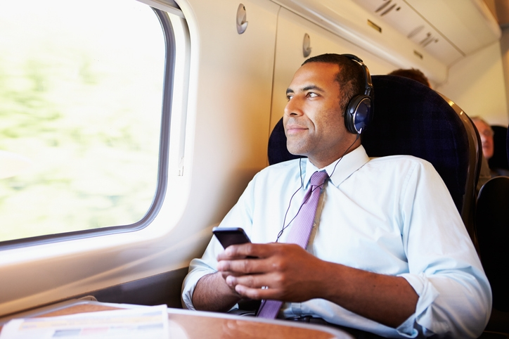 Man on train wearing headphones while looking out the window